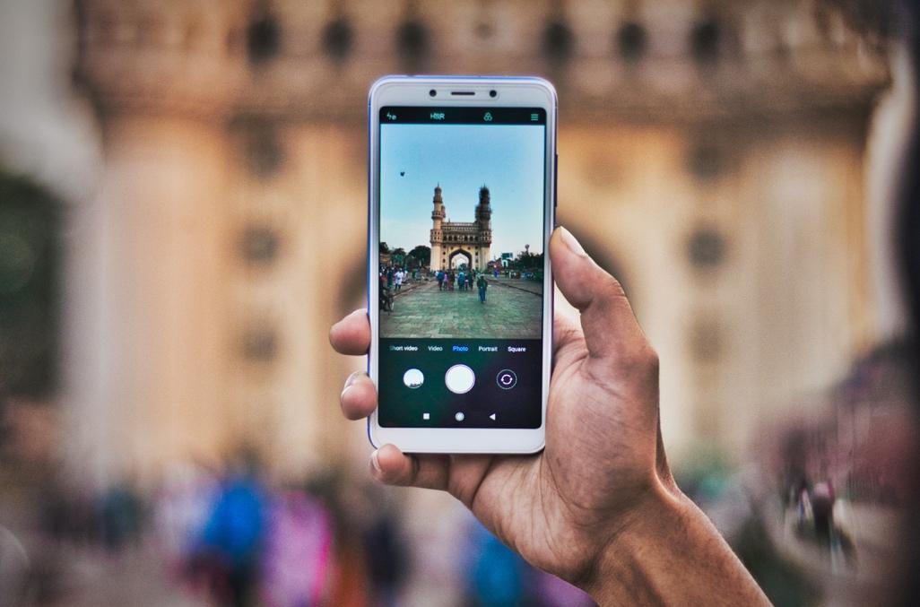 Et bilde som inneholder person, mobil, telefon, holder Automatisk generert beskrivelse